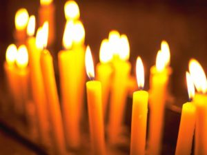 Many small taper candles burning.