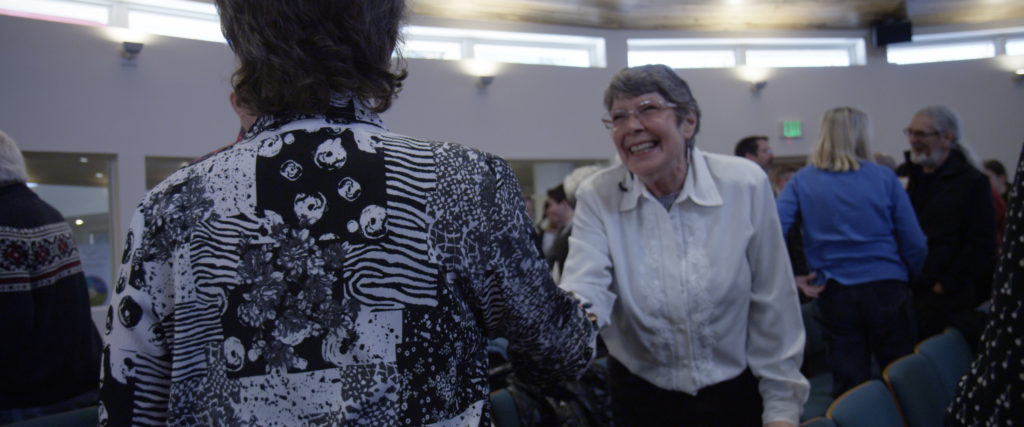 Church members greeting each other with smiles