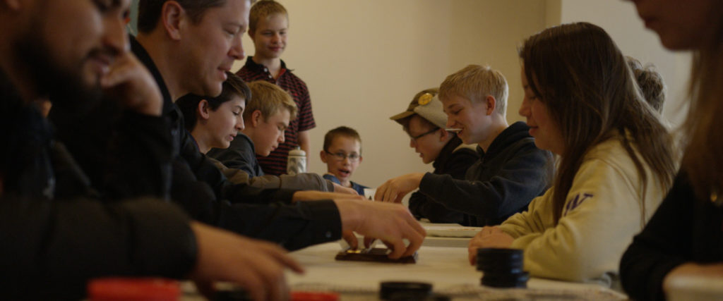 Several middle school youth play board games with adult mentors.